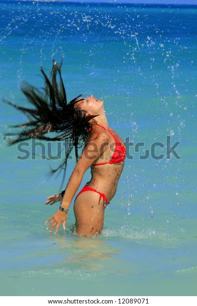 A pretty young woman at the beach playing in the water