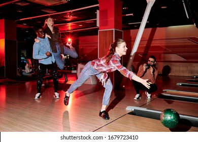 Pretty young woman bending over alley and throwing bowling ball while her friends taking photo and expressing joy during game