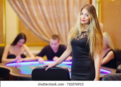 Pretty young woman in black dress poses in casino, three people play poker out of focus