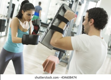 Pretty young woman boxing in the gym with trainer