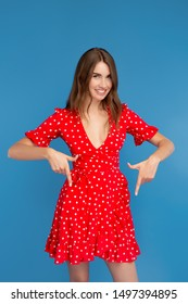 Pretty young woman with bright smile in red dress pointing fingers down over blue background.