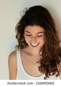 Pretty young woman with brown curls looking down and laughing in happiness against plain wall