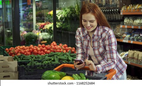 Pretty young woman browsing her shopping list on her smartphone at the supermarket. Attractive redhead girl flipping on her cellphone. Caucasian female customer holding her phone over the grocery cart