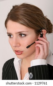 Pretty young woman in business attire talking on a phone headset.