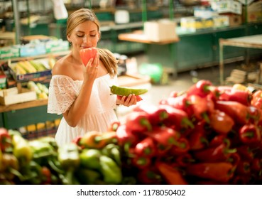 Pretty young woman buying fresh vegetables on the market