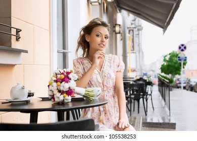 A pretty young woman in a cafe. Outdoors