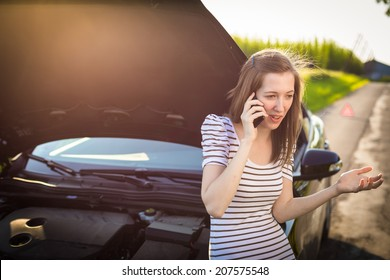 Pretty, young woman calling the roadside service/assistance after her car has broken down