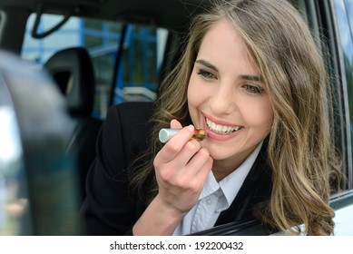 Pretty young woman in a car doing makeup.