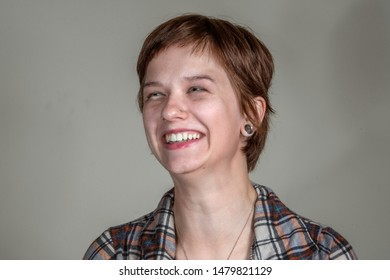 A pretty young woman in a casual flannel shirt looks amused,  in a head-and-shoulders studio shot.