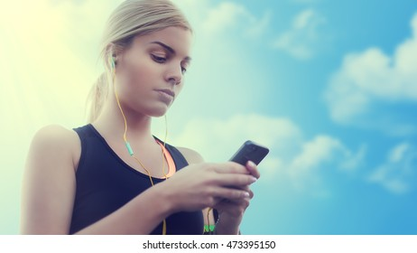 Pretty young woman chooses music before jogging. Fitness concept. Lens flare. Colorized