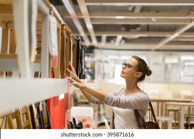 Pretty, young woman choosing the right furniture for her apartment in a modern home furnishings store (color toned image; shallow DOF)