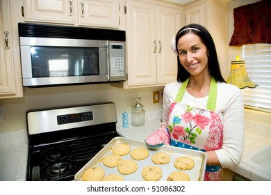 A pretty young woman in a colorful apron is baking cookies in her clean, modern kitchen