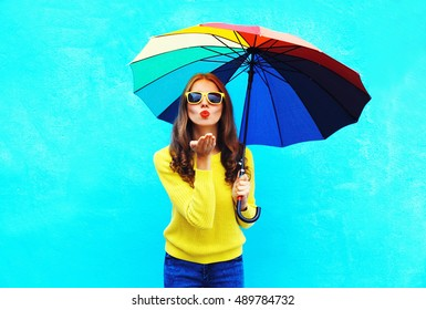 Pretty young woman with colorful umbrella sends air sweet kiss in autumn day over blue background wearing a yellow knitted sweater