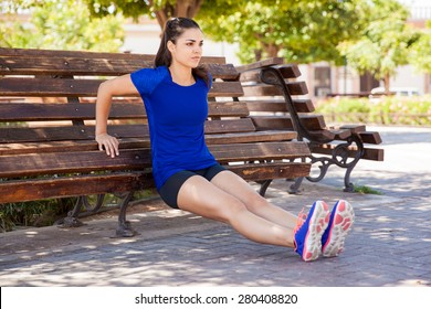 Pretty young woman concentrating on her workout, leaning on a park bench