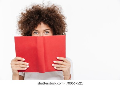 Pretty young woman with curly hair peeking out of a book and looking at camera isolated over white background
