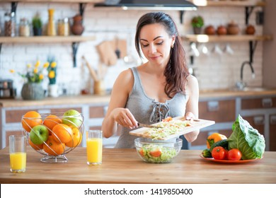 Pretty young woman cutting vegetables salad in the kitchen