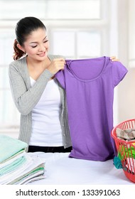 Pretty young woman doing the laundry at home