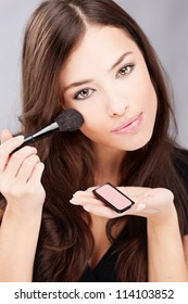 pretty young woman doing make up with powder brush