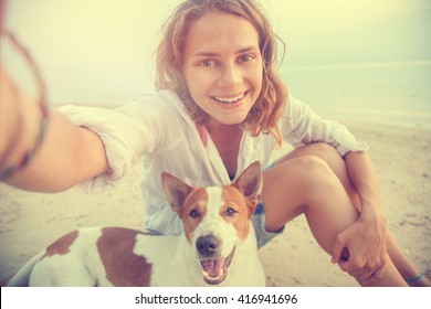pretty young woman doing selfie with her dog on the beach at sunset