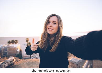 Pretty young woman doing selfie near the ocean. Concept of happiness and inspiration of travel.