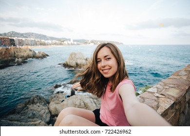 Pretty young woman doing selfie near the sea. Beautiful female student takes photo for travel blog.