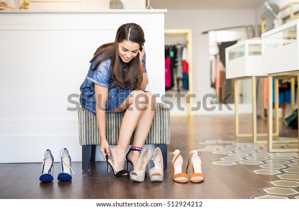Pretty young woman doing some shopping and trying on a few pairs of high heels at a fashion store