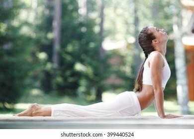 Pretty young woman doing yoga exercise in the park
