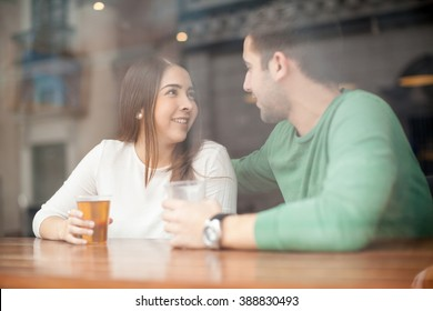 Pretty young woman drinking beer at a bar and talking to a guy