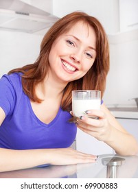 pretty young woman drinking milk in the kitchen at home