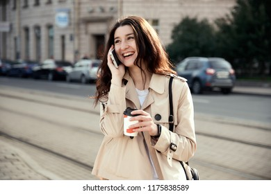 Pretty young woman drinking takeout coffee cup outdoors, talking on the phone, smiling, rejoice.