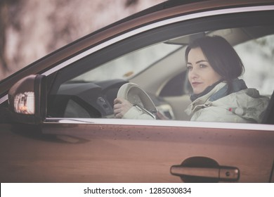 Pretty, young woman  driving a car -Invitation to travel. Car rental or vacation.