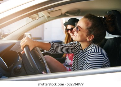 Pretty young woman driving a car with a friend smiling as they enjoy a chat together while passing through town