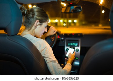 Pretty young woman driving her new car  - taking rick -  using her smart phone while driving