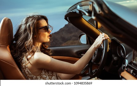 Pretty, young woman driving her modern car at the evening