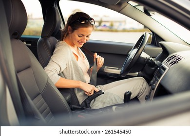 Pretty young woman driving her new car  (color toned image; shallow DOF)