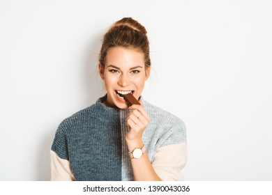 Pretty young woman eating chocolate bar, studio image taken on white background