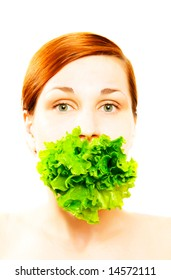 Pretty young woman eating lettuce