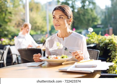 Pretty young woman eating out on restaurant terrace