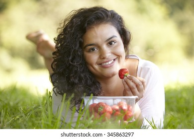Pretty Young Woman Eating Strawberries Outdoors