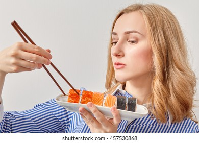 pretty young woman eating sushi looking at camera