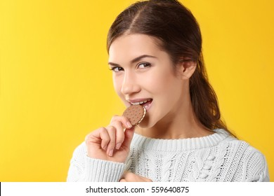 Pretty young woman eating tasty cookie, on yellow background