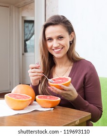 Pretty young woman eats grapefruit with spoon at home interior