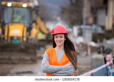 Pretty young woman engineer standing in front of excavator at construction site