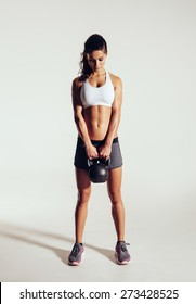 Pretty young woman exercising crossfit with kettle bell weight. Crossfit female working out on grey background. Focused female athlete doing body building exercise on grey background.