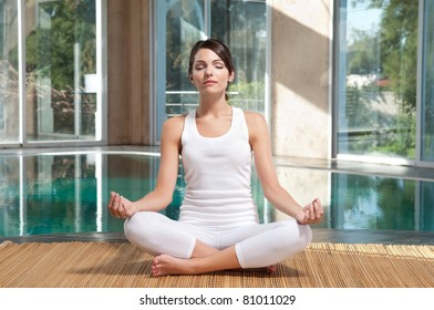 Pretty young woman with eyes closed doing yoga exercise on mat