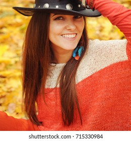 Pretty young woman fashion close up portrait, leather hat and handmade earrings, outdoor in autumn park