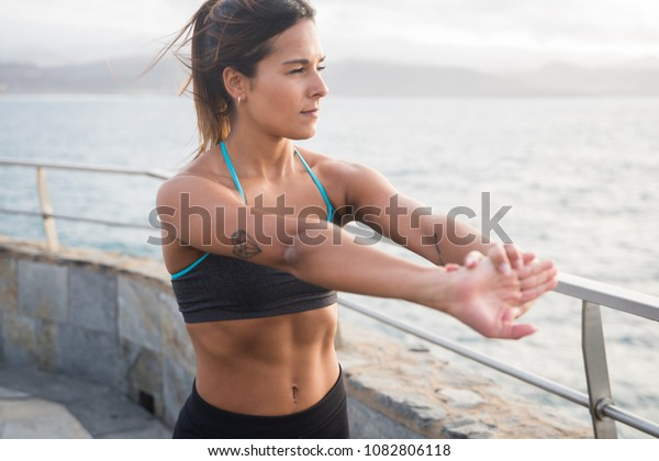A pretty young woman in fitness clothing stretching her arms out while looking out at the sea