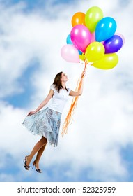 Pretty young woman flying on colorful balloons in the sky