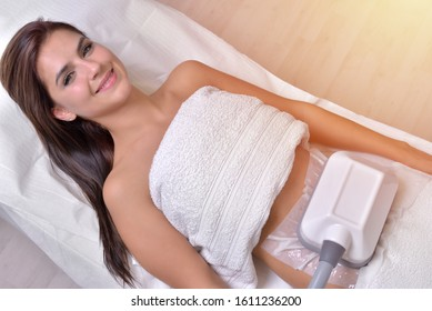 Hübsche junge Frau, die eine Kryolipolytherapie im Kosmetikschrank erhält