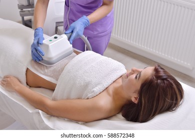 Pretty young woman getting cryolipolyse fat treatment in professional cosmetic cabinet